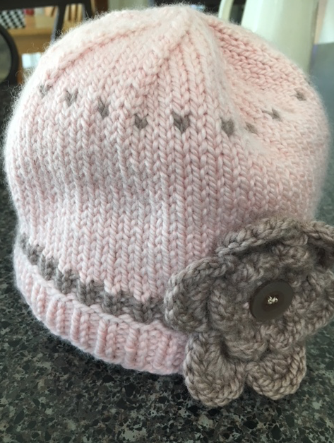 Little knit baby hat in pink with crocheted flower