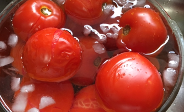 Whole red tomatoes in ice water