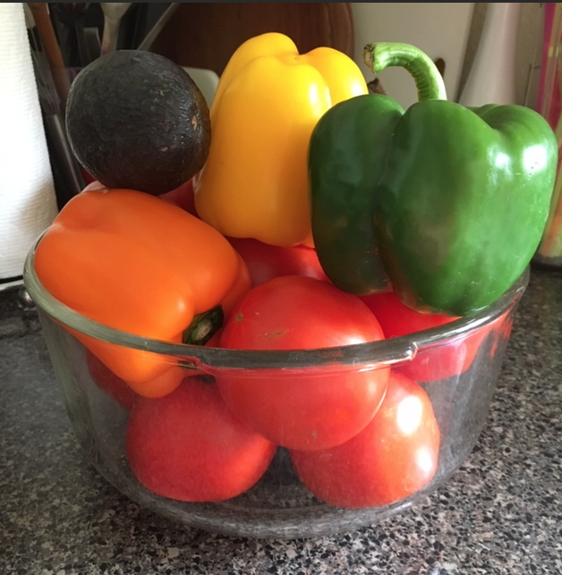 Bowl of fresh tomatoes, bell peppers and avocado
