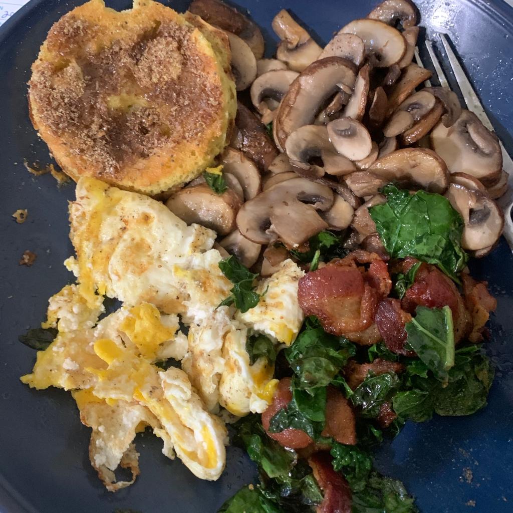 Keto breakfast food eggs, mushrooms, bacon, kale and biscuit